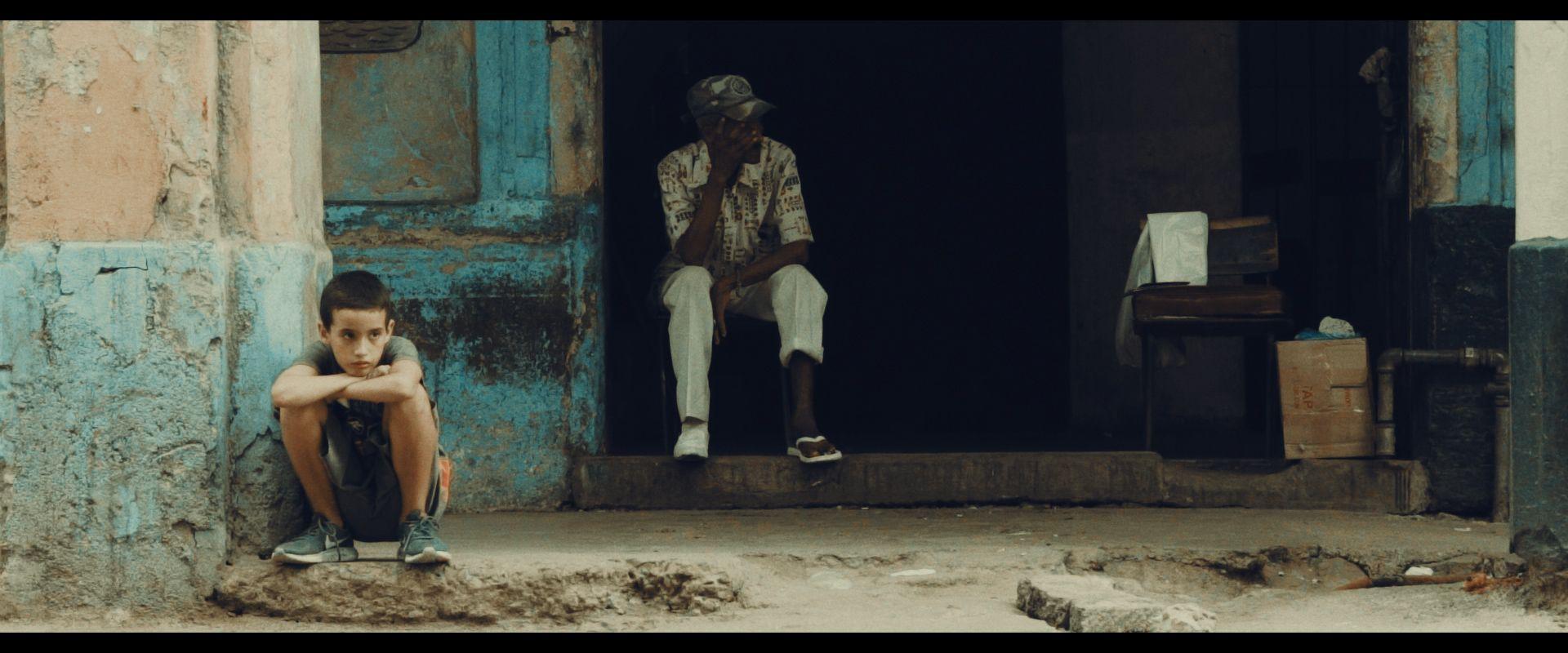 ein Junge sitzt auf einer maroden Türschwelle